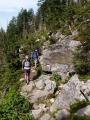 K Luznému vede cesta spíš bukovým lesem a tak vedro ještě moc nevnímáme. U Čertovy rokle se na nás z hlubin kamenného moře dokonce line ledový dech.