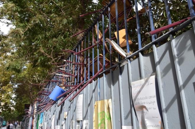Nejsem si jist, zda ozdobení školního plotu židlemi nějak souvisí s vylepenými protinásilnými plakáty